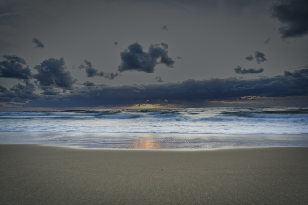 grey and blue clouds over beach at sunset