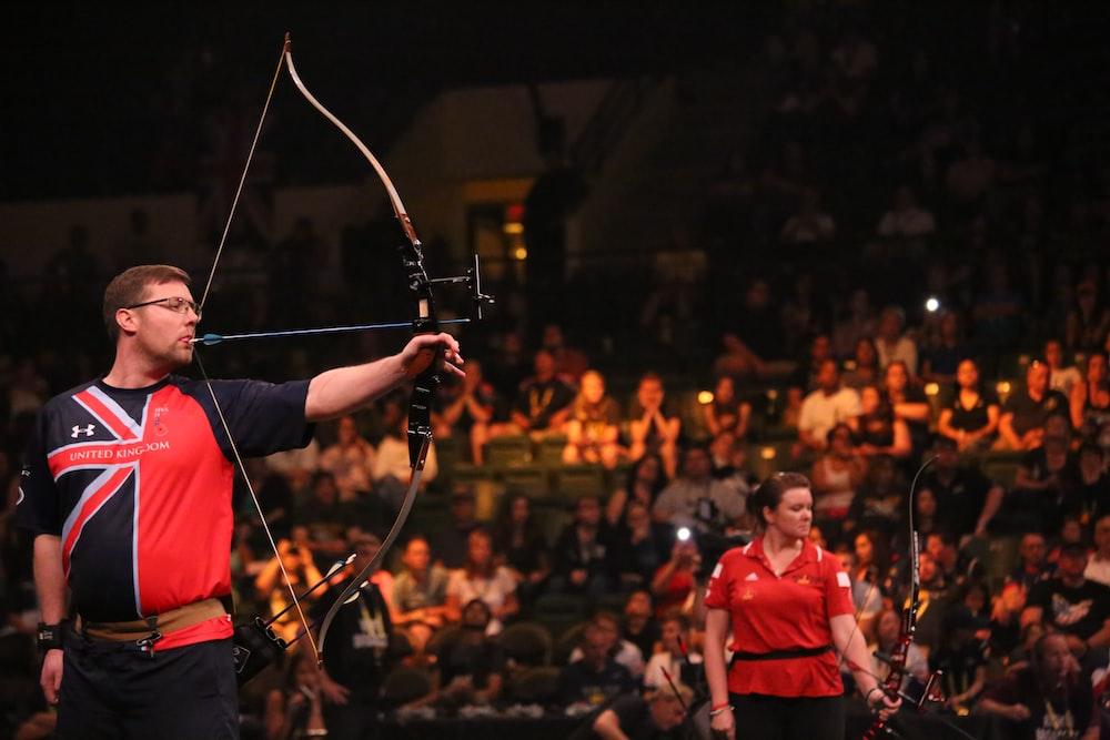 man doing archery near woman holding bow
