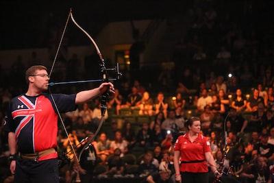 man doing archery near woman holding bow archery zoom background