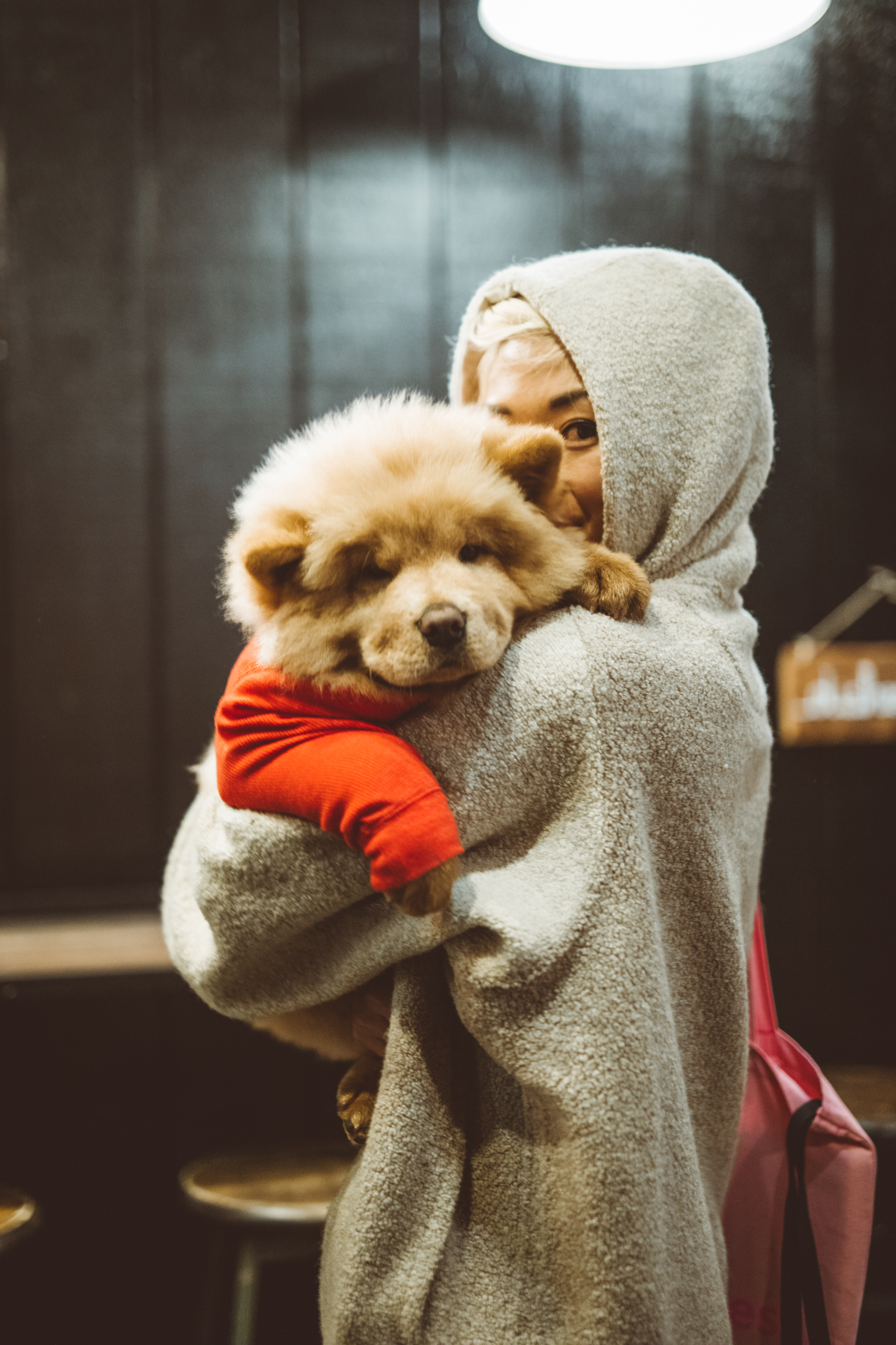 woman carrying beige dog