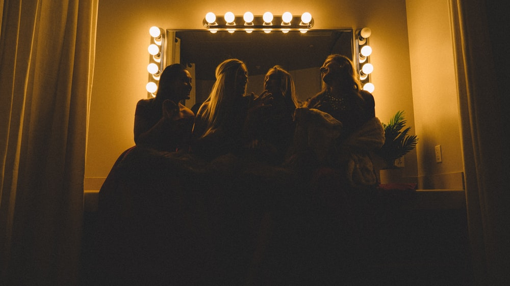 four women sitting infront of vanity table