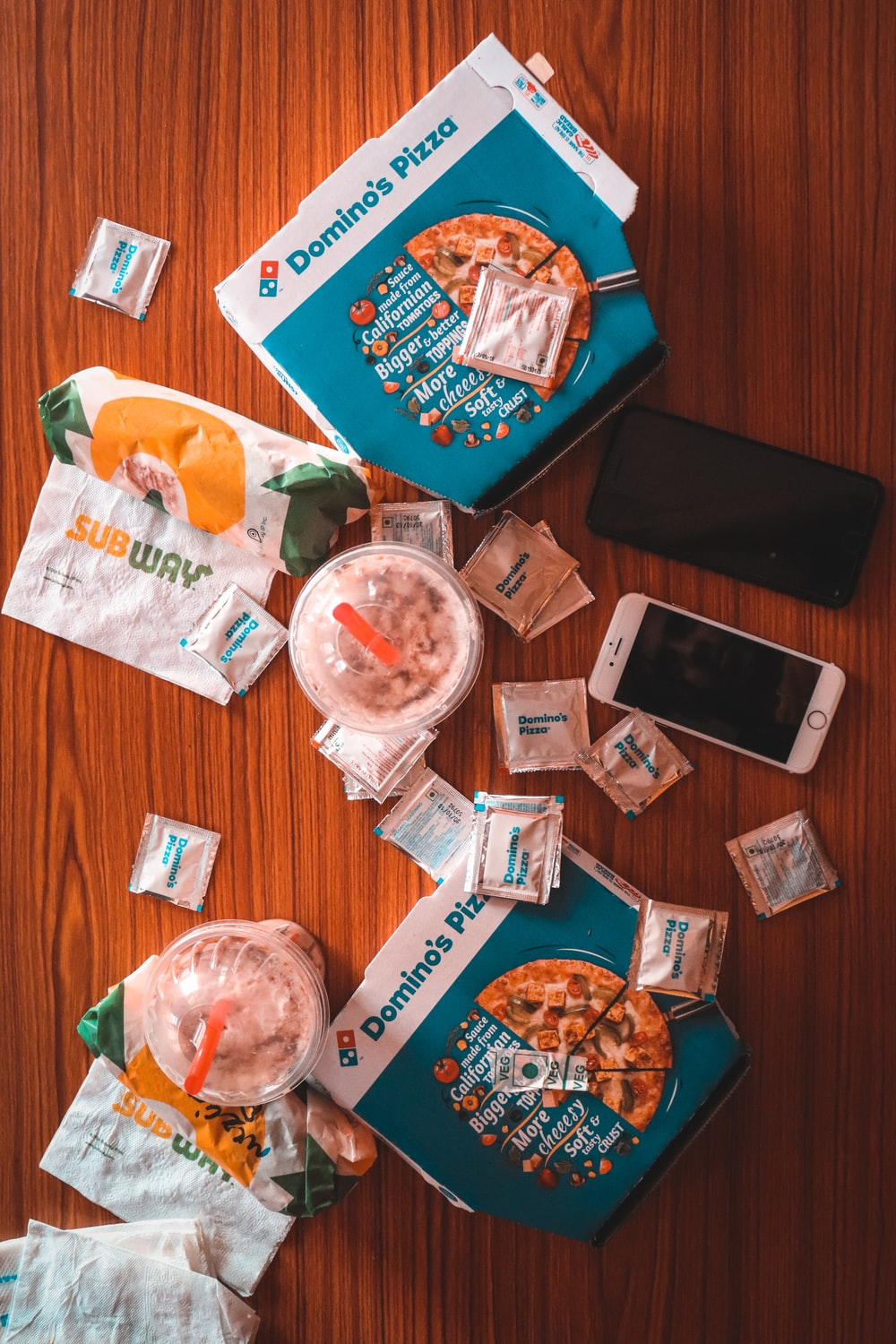 pizza and sauce packs beside iPhone on table