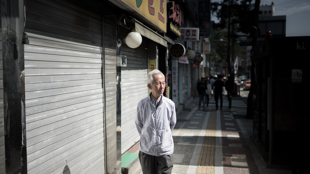 man walking near roller shutter