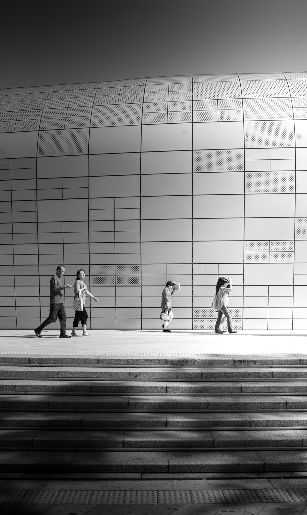 grayscale photo of people walking near building
