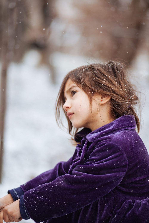 girl wearing purple jacket across blurry background