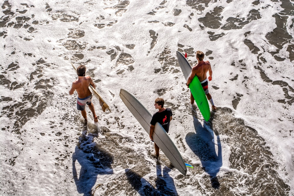 three men about to surf