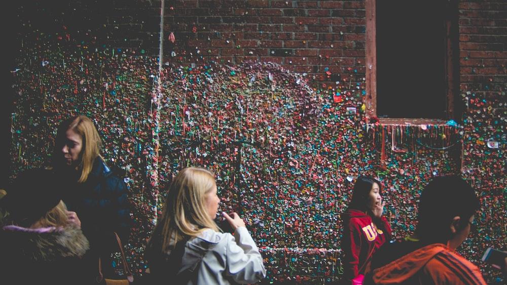 people beside red brick building