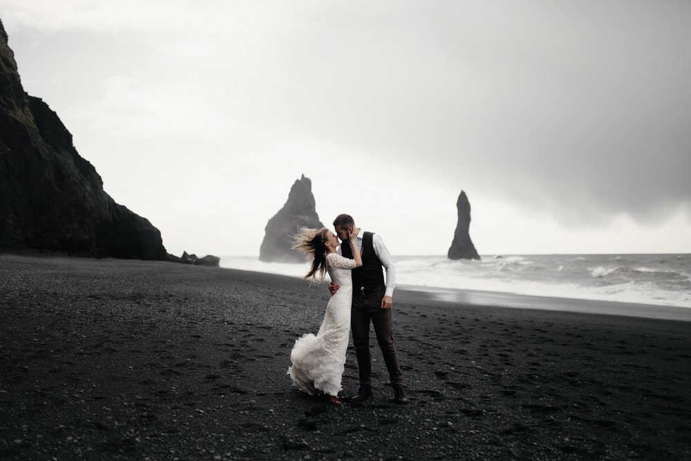 grayscale photography of groom and bride kissing on beach