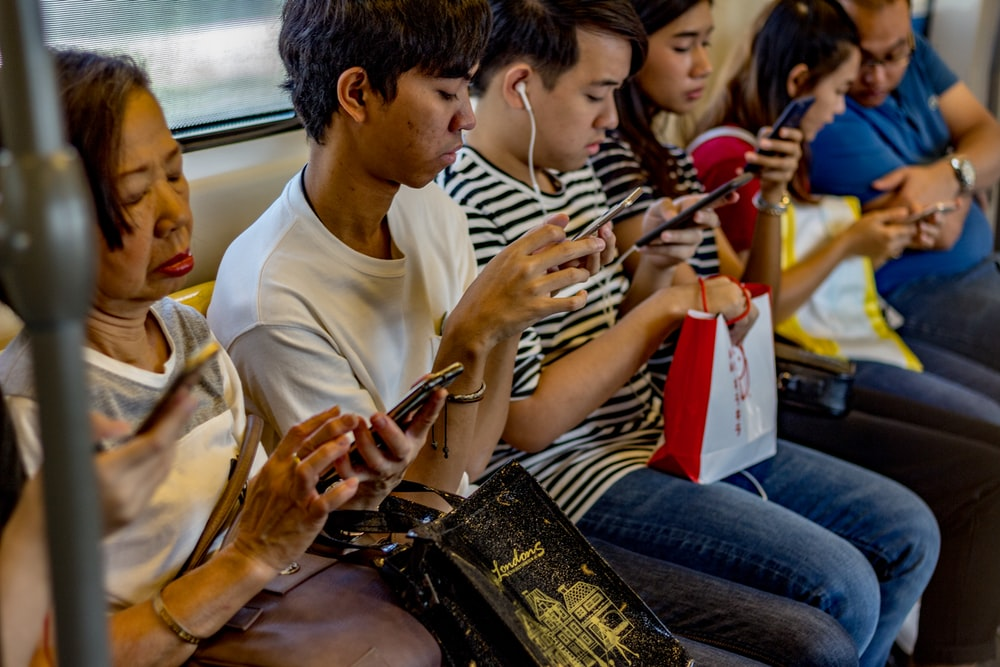people using smartphones while sitting inside train