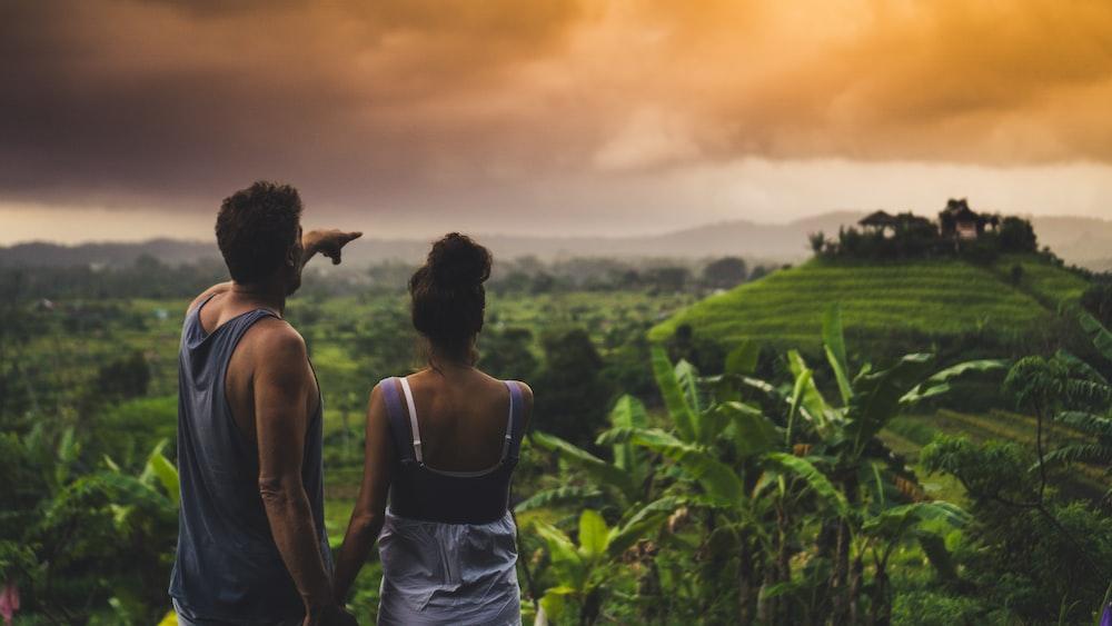 man and woman looking at hill