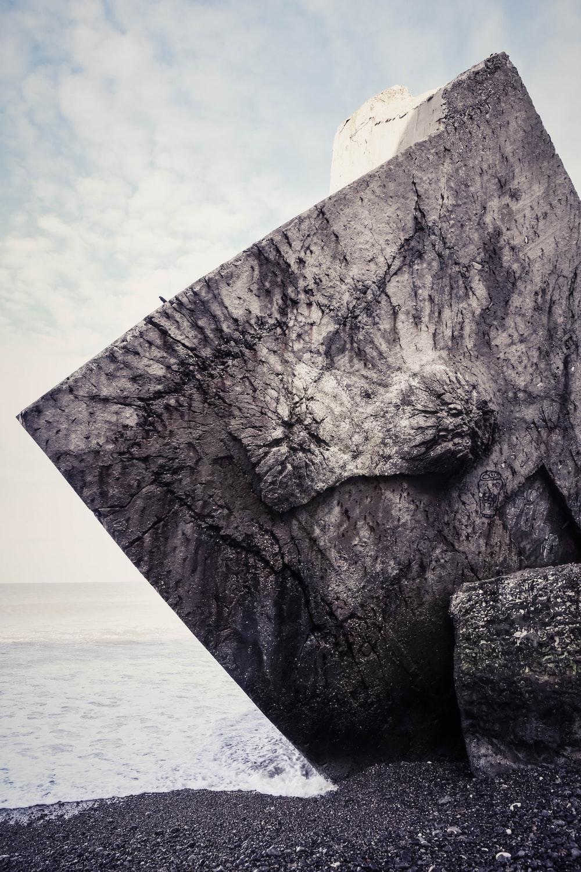 gray rock across body of water