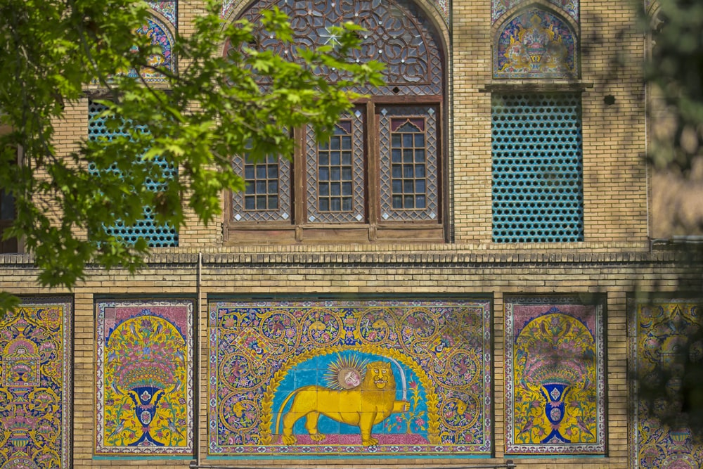 multicolored lion art on building's wall at daytime