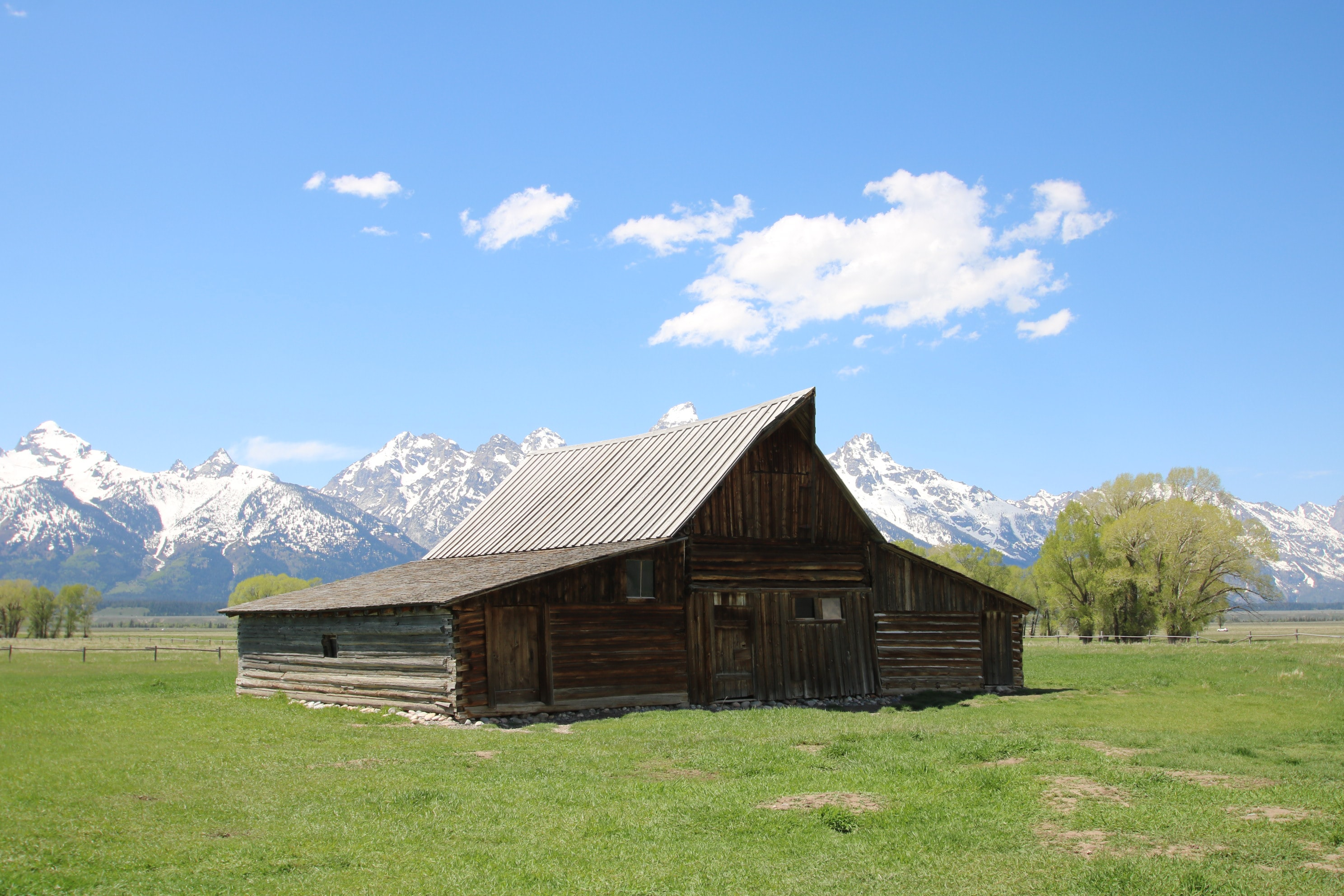 brown wooden barn near snow-covered mountain during day time