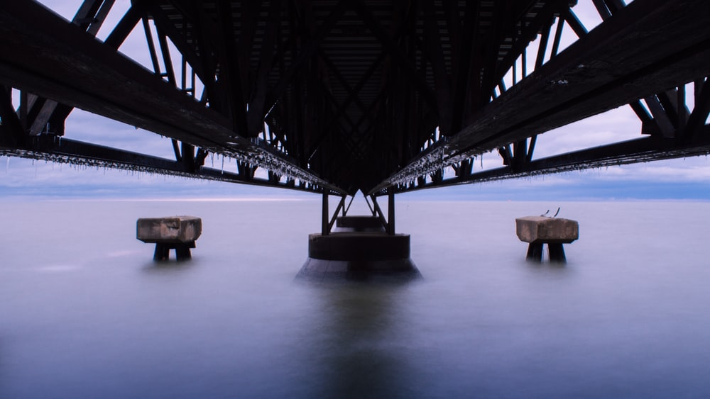 low-angle photography of black steel bridge