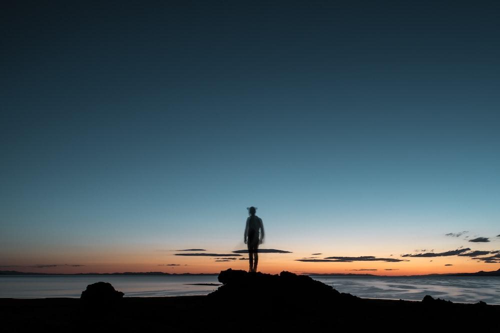 sillhouette of a man facing the beach