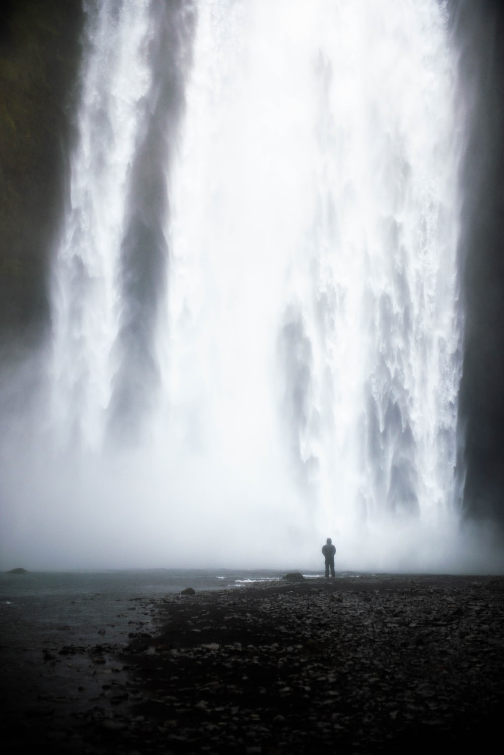 man standing in front of waterfalls