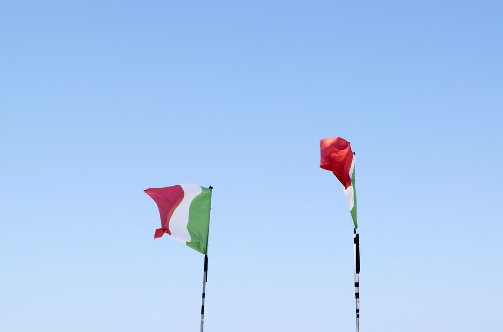 two flags of Italy on flag poles