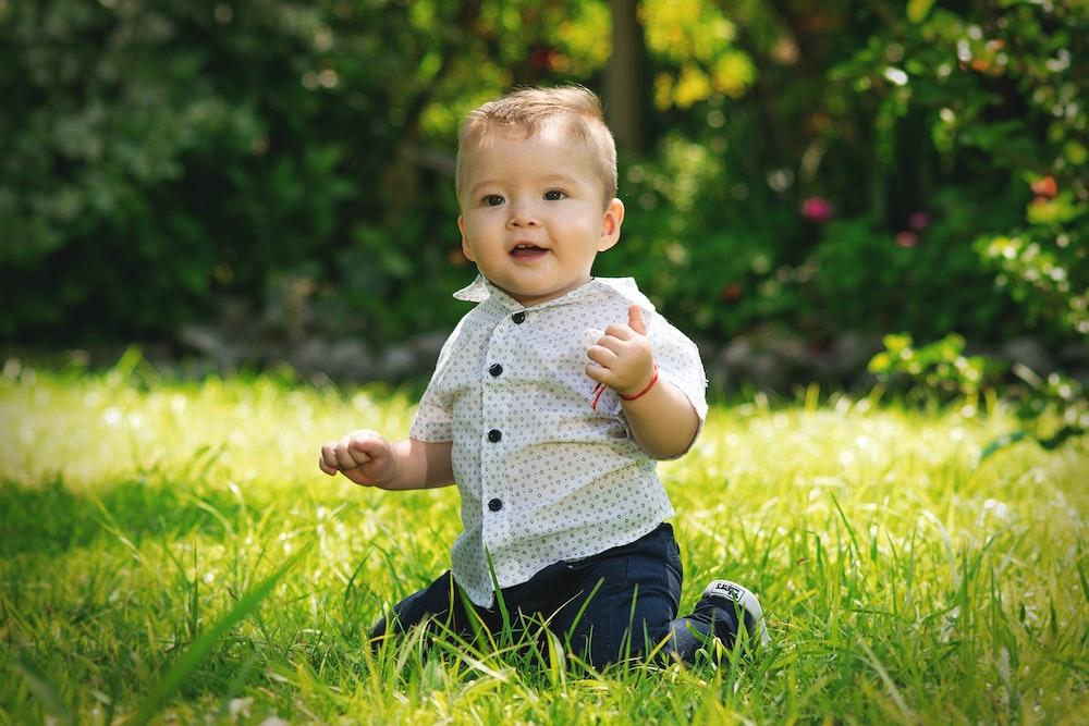 baby kneeling on grass