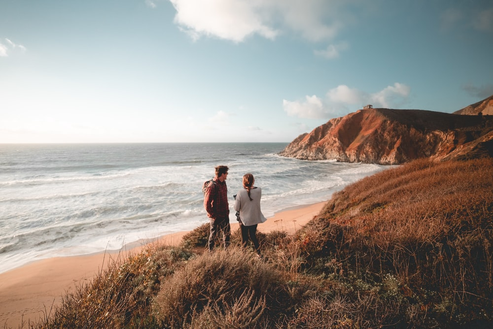 man and woman standing on brown grass field near ocean