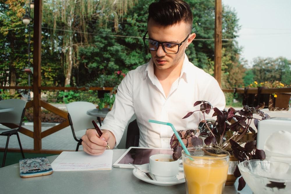 man wearing white dress shirt writing on white paper
