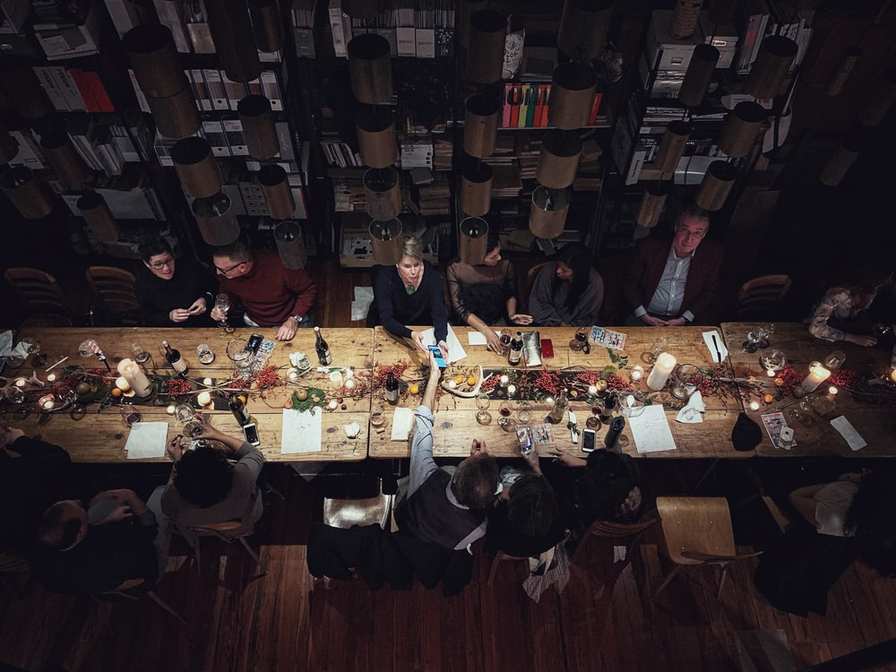 high-angle photography of people beside table