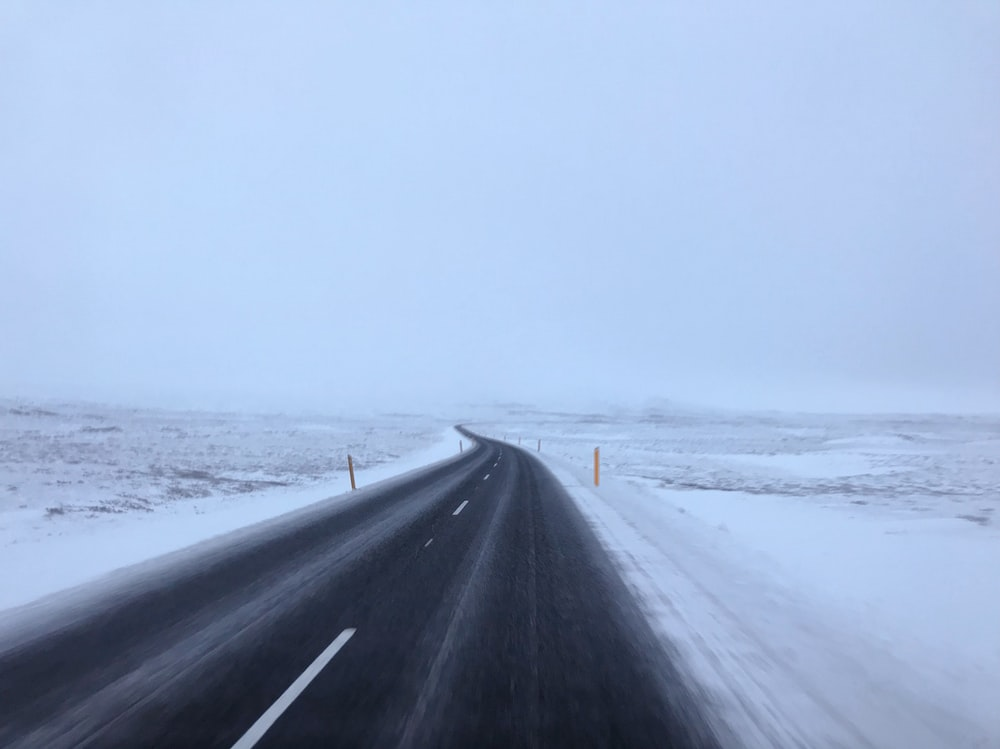empty road between snow covered land