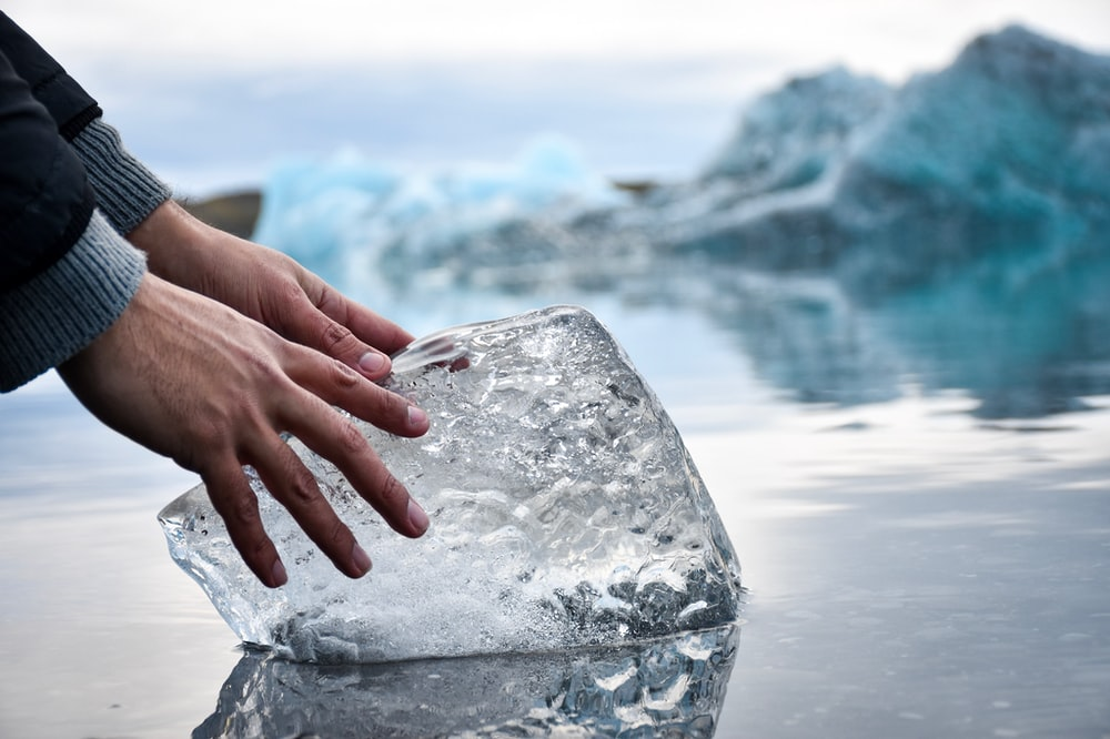 person with hands on ice block on water during daytime