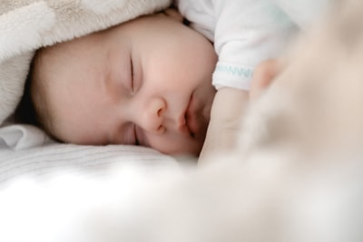 selective focus photography of sleeping baby baby zoom background