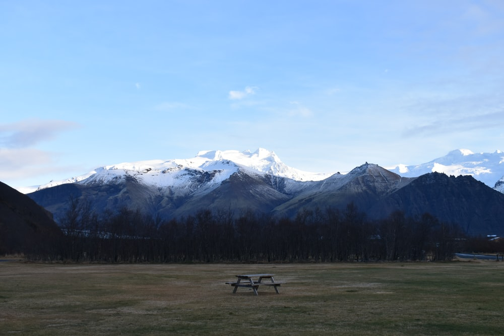 wooden picnic table in the middle of grass field overlooking snow-caped mountains