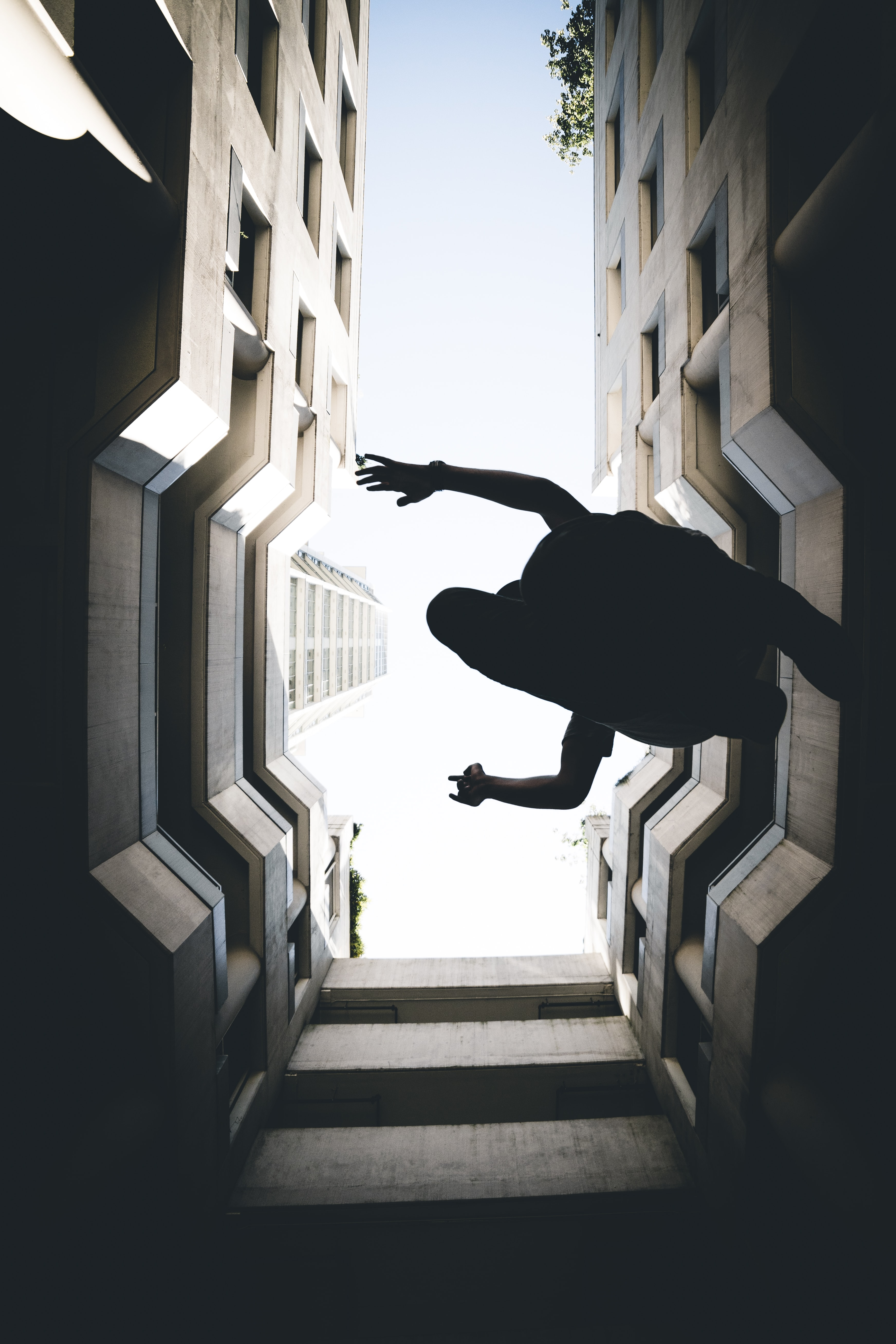 man leaps in middle of high-rise buildings