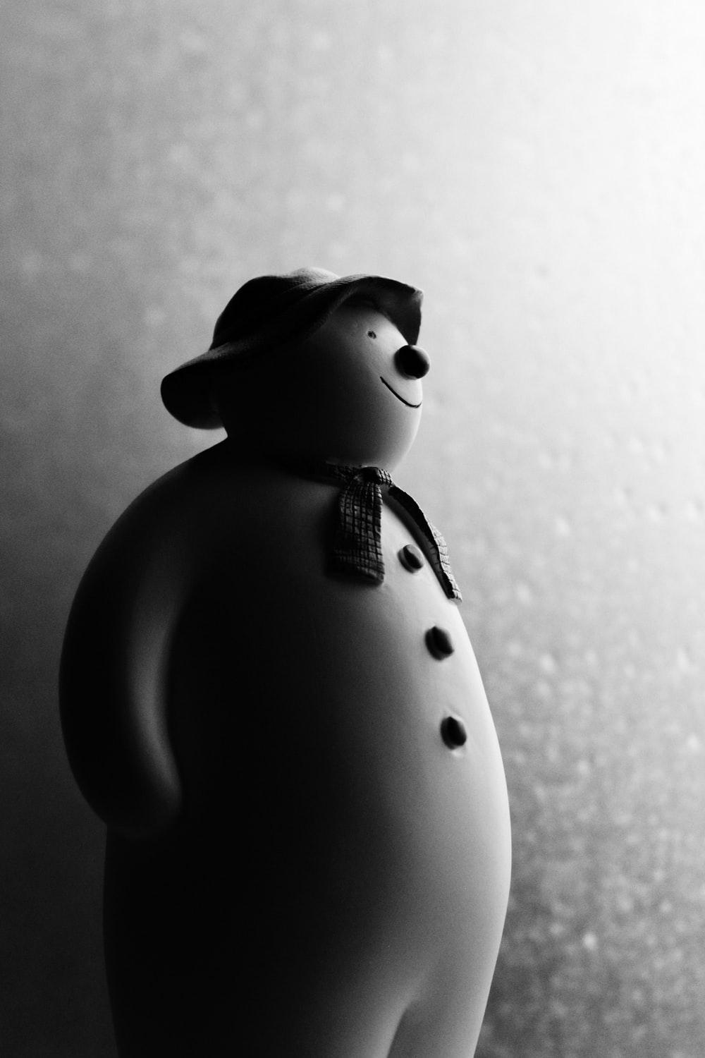 grayscale photography of snowman figurine