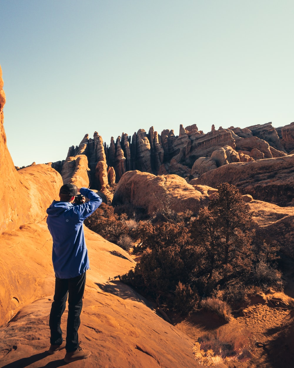 man in blue hoodie taking pictures ob the rock formation