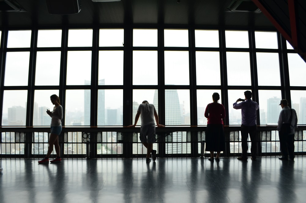 five people standing in front of window
