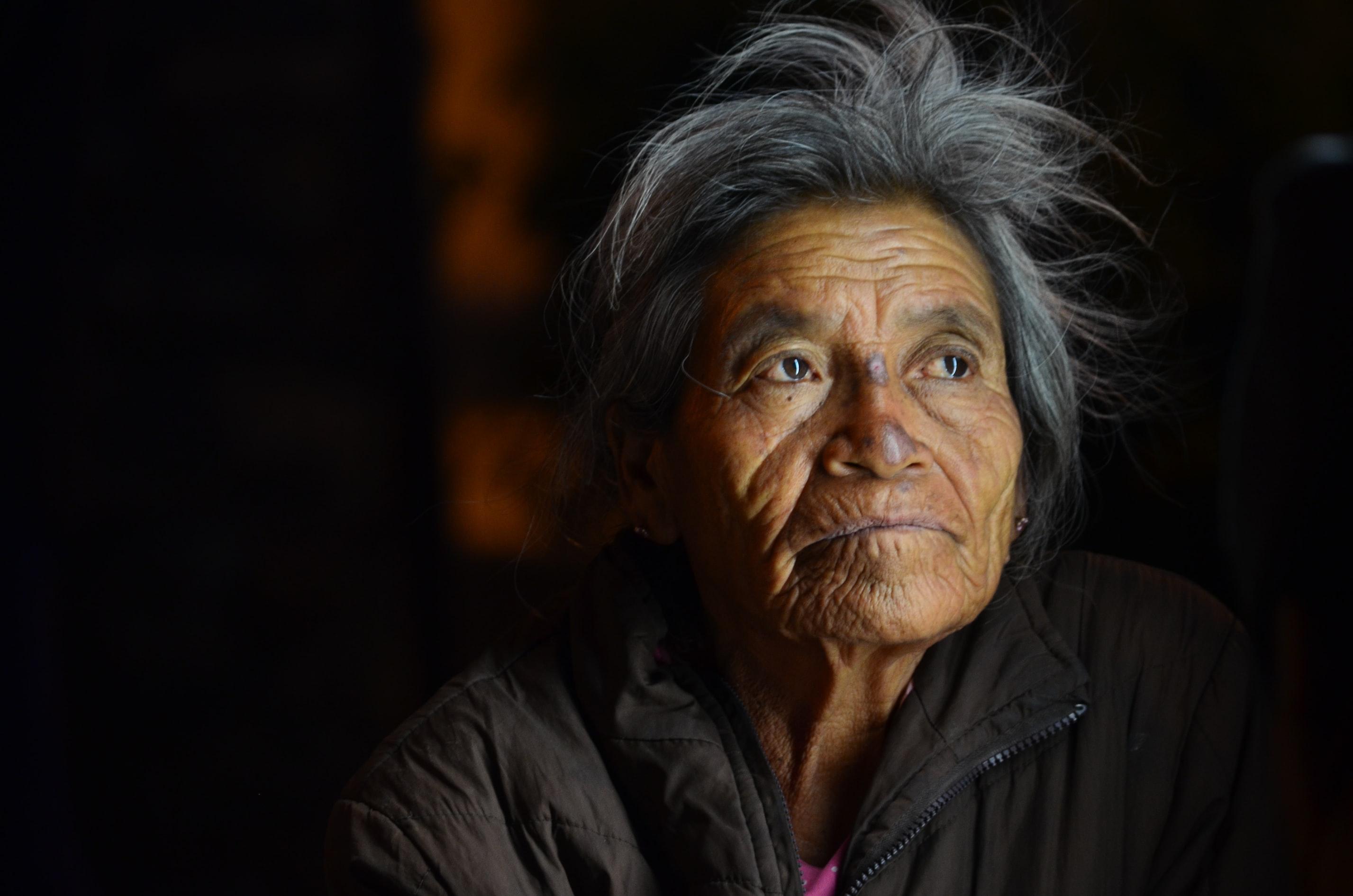 Old woman wearing a black zip jacket