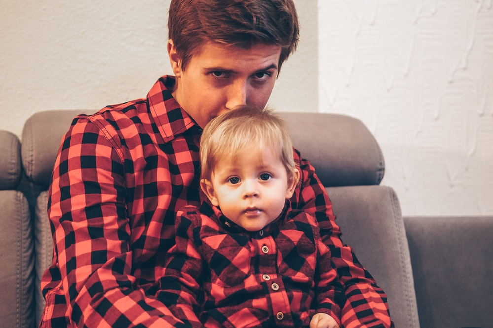 man wearing black and red plaid shirt kissing toddlers head wearing matching top