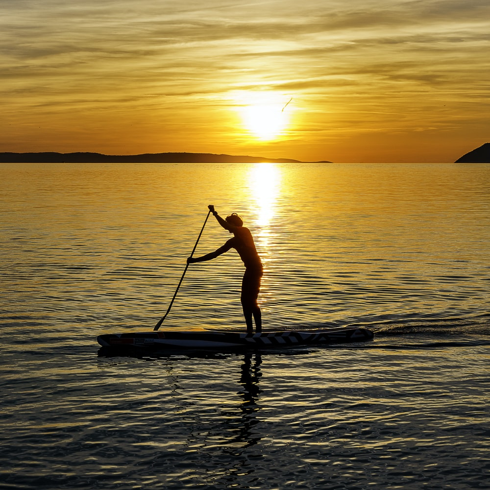 man on kayak during sunset