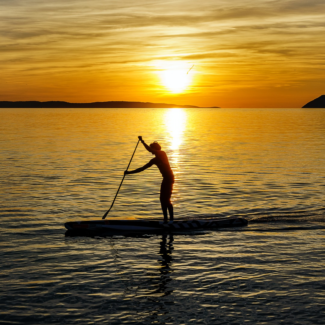 Paddling into the Sunset on the surfing board.