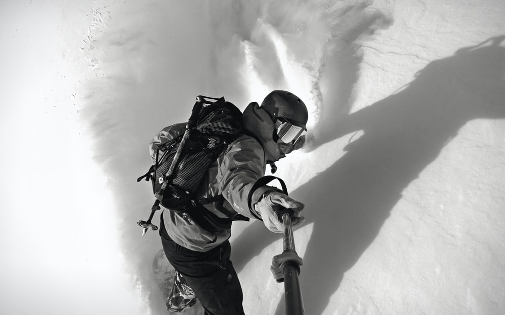 man wearing snow hiking outfit taking a selfie using monopod