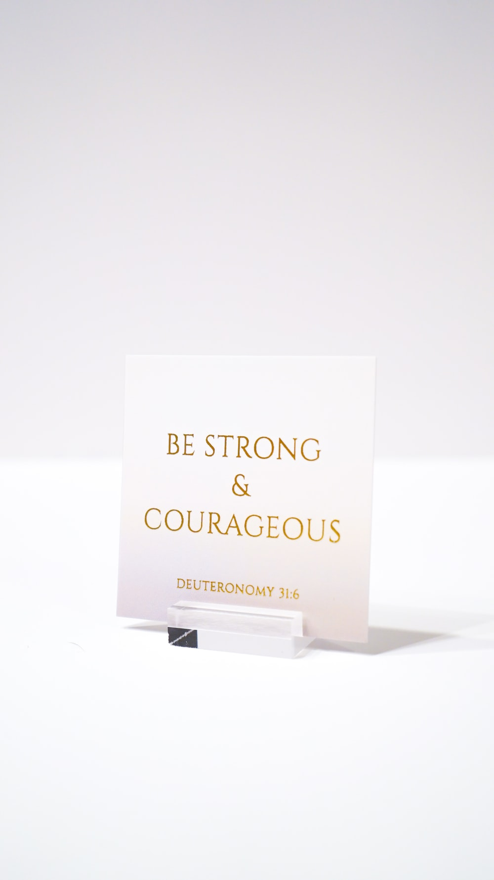 white paper with be strong and courageous printed text