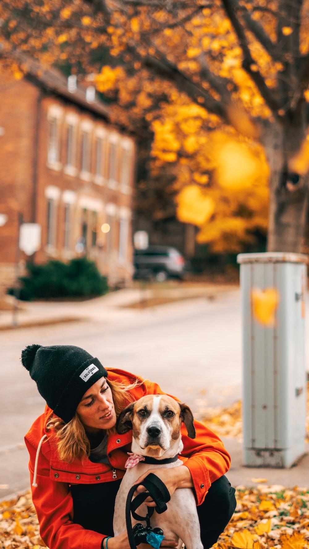 woman wearing orange jacket hugging brown dog