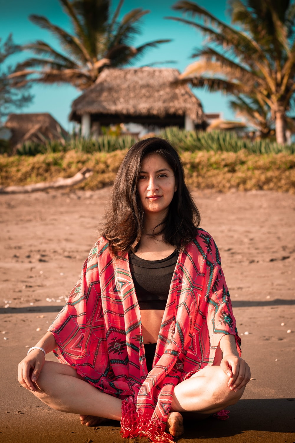 woman wearing black crop top and black shorts Indian sitting on beach sand during daytime