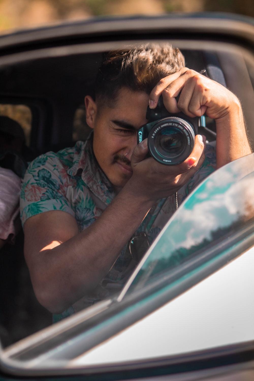 man holding camera inside vehicle