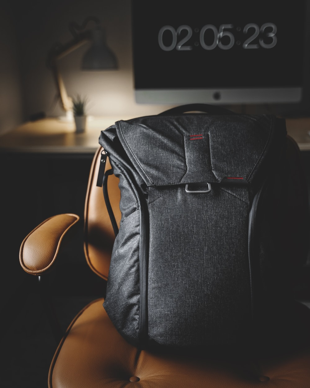 black backpack on brown leather armchair