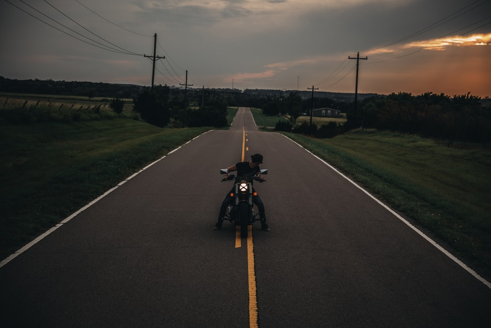 man riding motorcycle on road during golden hour
