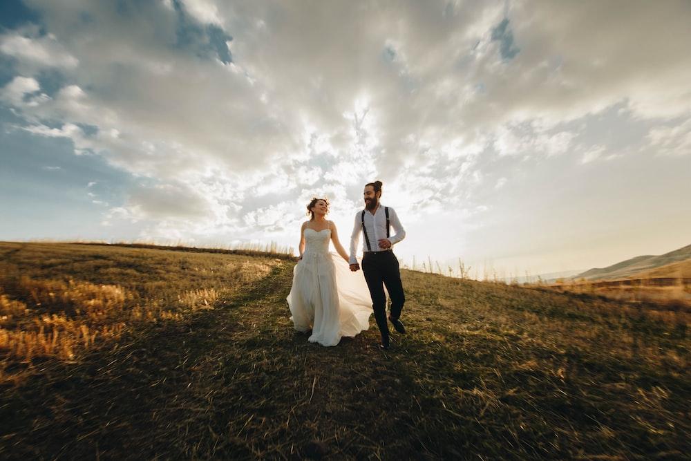 groom and bride running along grass field