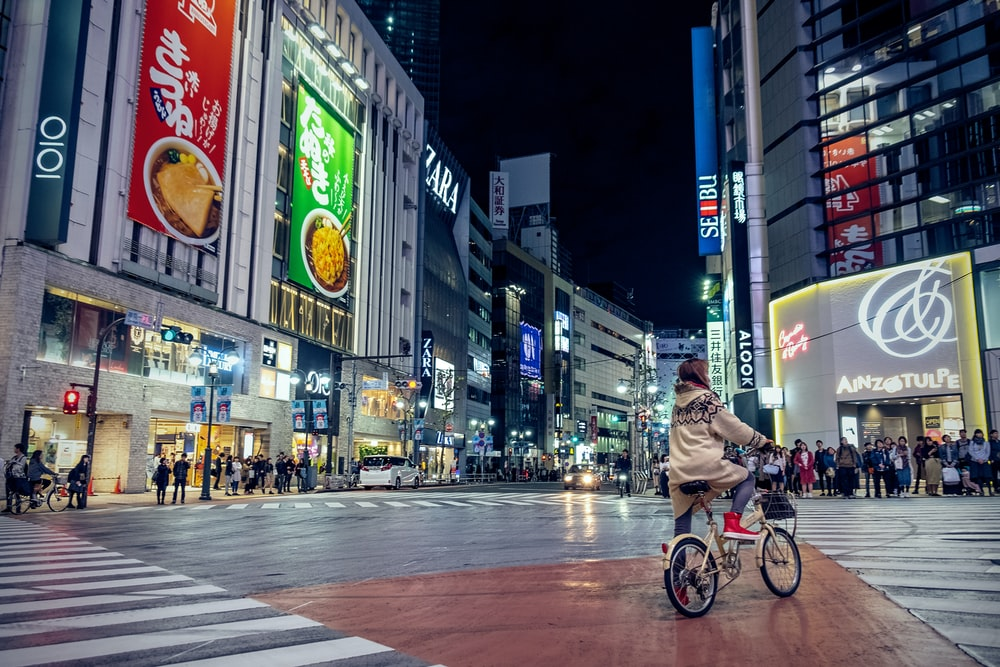 woman riding bicycle in intersection at night