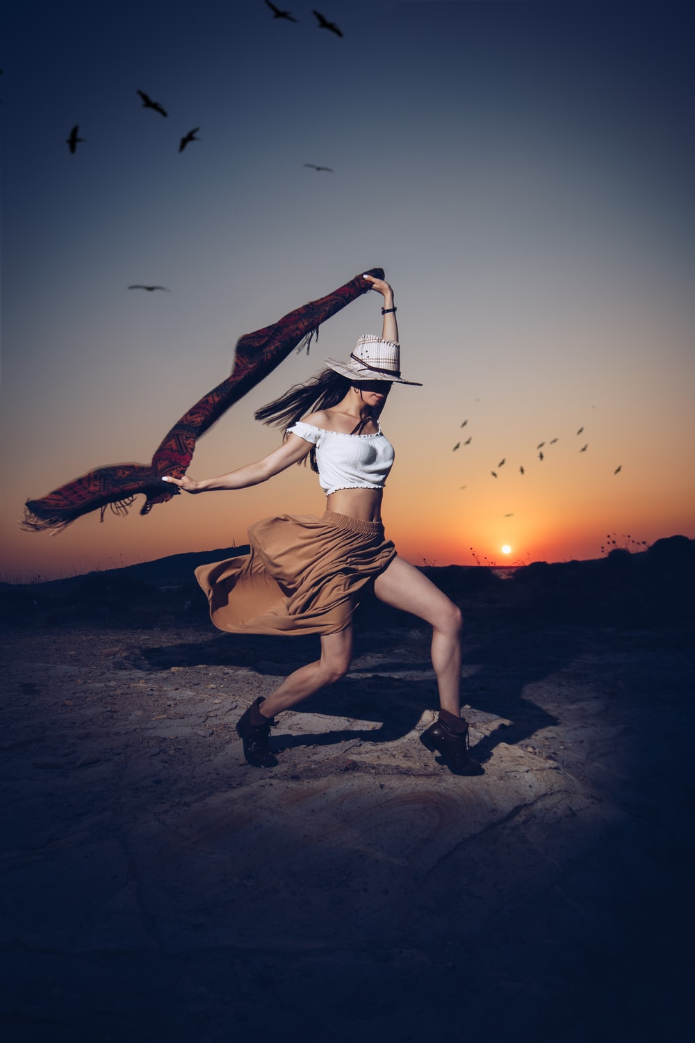 woman posing while holding red and black scarf during sunset