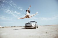 woman jumping in front of parked silver vehicle under clear blue sky during daytime