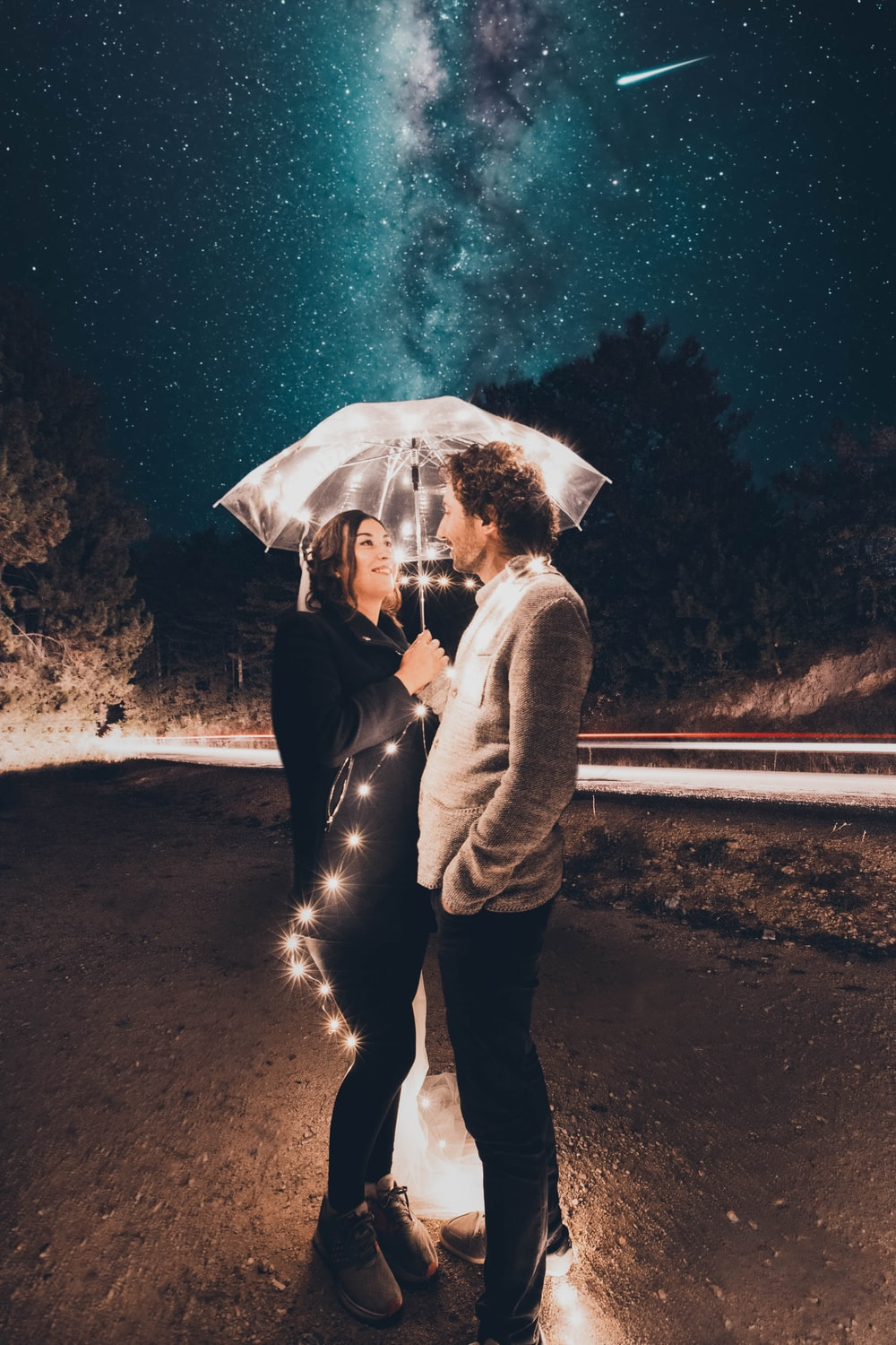 Couple under clear umbrella with string lights during night