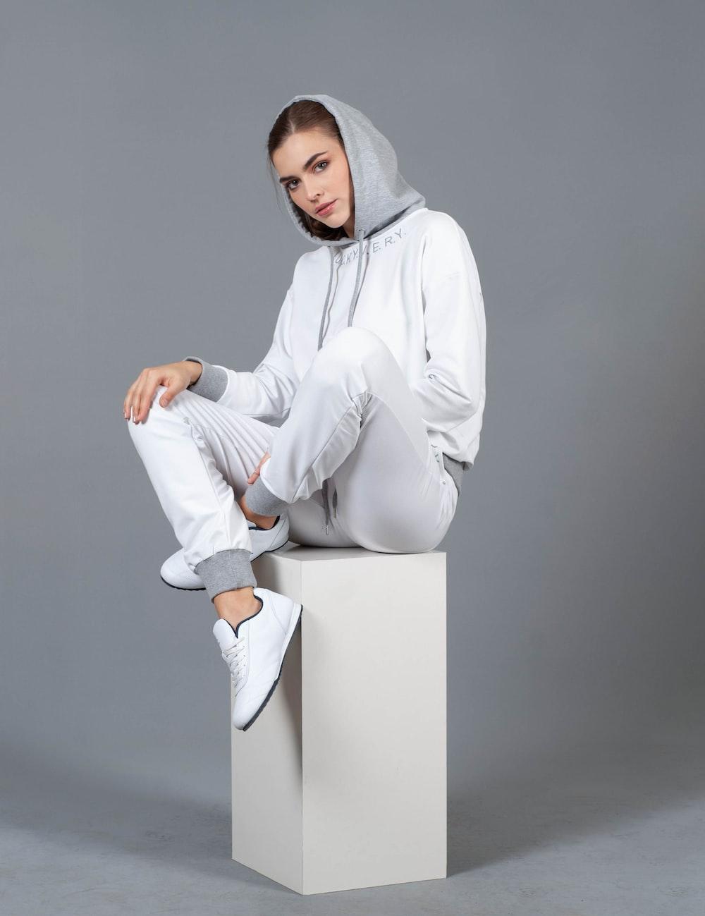 woman sitting on white box
